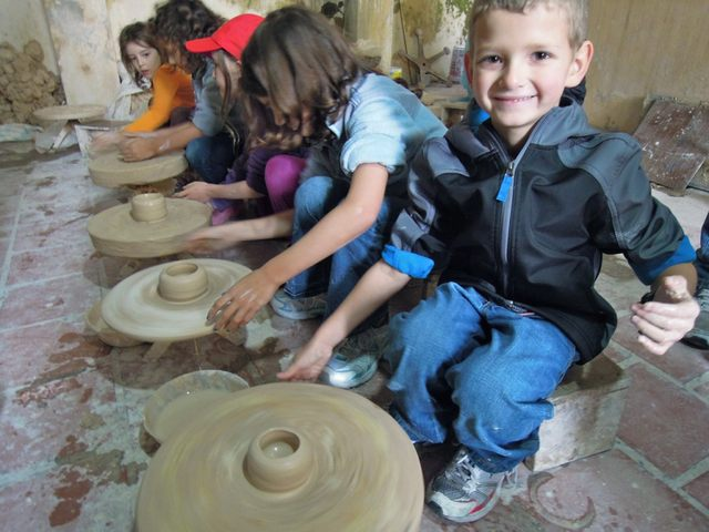 The foreign children turn the pottery wheels by hand