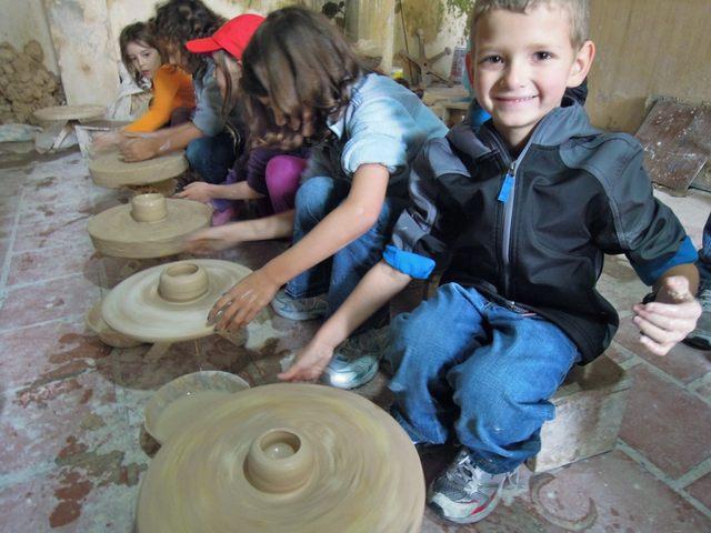 Иностранные дети превратить гончарное колесо вручную